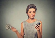 Ongelukkige jonge vrouw die slimme telefoon bekijken die weg de rekeningen van de contant gelddollar werpen stock foto's