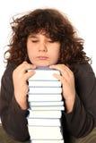 Ongelukkige jongen en vele boeken Stock Foto's