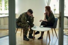 Ongelukkige militair in groene eenvormig en psychotherapist tijdens overleg in het bureau royalty-vrije stock afbeelding