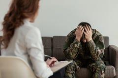 Ongelukkige militair met depressie en emotioneel probleem tijdens therapie met psychotherapist royalty-vrije stock afbeeldingen
