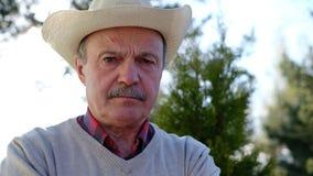 Ongelukkige oude Spaanse mens die in hoed zijn gezicht fronsen stock videobeelden
