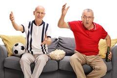 Ongelukkige oudsten die op voetbal letten Royalty-vrije Stock Foto