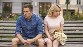 Ongelukkige paarzitting na strijd, meisje met bloemen, probleem in verhouding royalty-vrije stock afbeelding