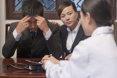 Ongelukkige Patiënt en Echtgenoot Betrokken over de Resultaten van de Arts Stock Fotografie