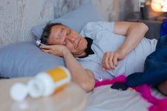 Ongelukkige rijpe mens die aan alcoholische intoxicatie lijden stock fotografie