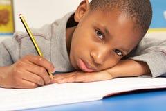 Ongelukkige Schooljongen die in Klaslokaal bestudeert Stock Fotografie