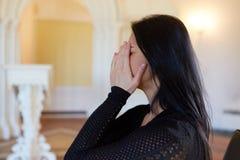 Ongelukkige schreeuwende vrouw bij begrafenis in kerk stock afbeeldingen
