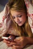 Ongelukkige Tiener die Tekstbericht verzenden terwijl het Liggen in Bed Stock Afbeeldingen