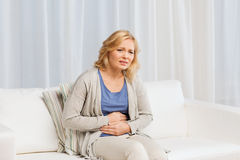 Ongelukkige vrouw die aan maagpijn thuis lijden Royalty-vrije Stock Fotografie