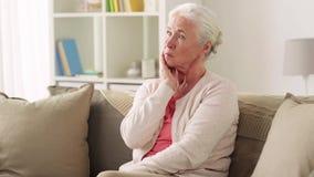 Ongelukkige vrouw die aan tandpijn thuis lijden stock footage