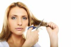 Ongelukkige vrouw die haar haar met geïsoleerde schaar snijden stock afbeelding