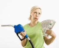 Ongelukkige vrouw met benzinepomp en geld. Stock Afbeeldingen