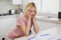 Ongelukkige vrouw met het zitten in keuken Royalty-vrije Stock Fotografie