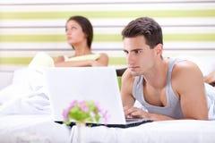 Ongelukkige vrouw omdat zijn echtgenoot die in bed werken Stock Afbeeldingen