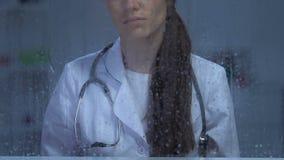Ongelukkige vrouwelijke arts die in regenachtig venster na geduldige dood, depressie kijken stock footage