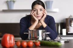 Ongemotiveerde vrouw die het diner voorbereiden stock foto
