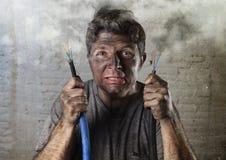 Ongeoefende mens die zich bij elektrokabel aansluiten die aan elektroongeval met vuil gebrand gezicht in grappige schokuitdrukkin royalty-vrije stock afbeeldingen