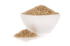 Ongepelde rijst in een kom die op wit wordt geïsoleerdt stock afbeelding