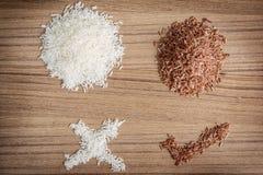 Ongepelde rijst en rijst op houten achtergrond Stock Foto's