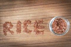 Ongepelde rijst in glas op houten achtergrond Stock Foto