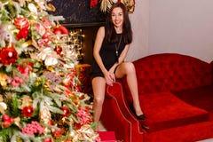 Ongeremde vrouwenzitting op de laagbenen wijd apart Vrouw en Kerstmis royalty-vrije stock afbeelding