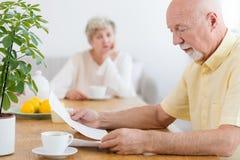 Ongerust gemaakt bejaarde die het bericht van betaling van schuld lezen stock afbeeldingen