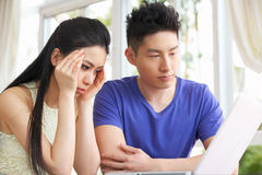 Ongerust gemaakt Jong Chinees Paar dat Laptop met behulp van Royalty-vrije Stock Afbeeldingen