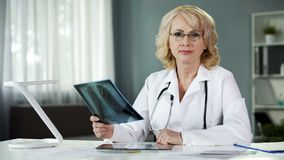 Ongerust gemaakt over de gezondheid van de patiënt arts die ernstig camera, geneeskunde onderzoeken royalty-vrije stock afbeelding