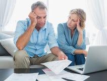 Ongerust gemaakt paar die hun laptop met behulp van om hun rekeningen te betalen Royalty-vrije Stock Foto's