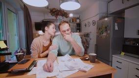 Ongerust gemaakt paar die hun rekeningen in de keuken thuis bekijken Man en vrouw die binnenlandse rekeningen berekenen stock videobeelden