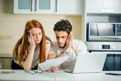 Ongerust gemaakt paar die hun rekeningen online met laptop thuis in woonkamer betalen stock foto