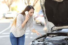 Ongerust gemaakte bestuurder met autoanalyse die verzekering roepen stock foto's