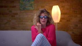 Ongerust gemaakte blondehuisvrouw die in roze sweater en 3D glazen verschrikkings op film letten bij comfortabel huis stock footage