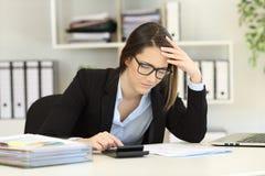 Ongerust gemaakte boekhouder het berekenen uitgaven op kantoor stock afbeelding