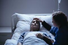 Ongerust gemaakte dochter die zwakke bejaarde moeder met kanker behandelen stock afbeeldingen