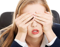 Ongerust gemaakte, droevige bedrijfsvrouwenzitting door de lijst. Royalty-vrije Stock Afbeelding