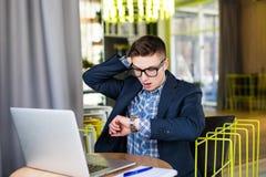 Ongerust gemaakte freelance zakenman die uit van tijd lopen die op de klok letten op kantoor Royalty-vrije Stock Foto's