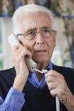 Ongerust gemaakte Hogere Mens die Telefoon thuis beantwoorden stock fotografie