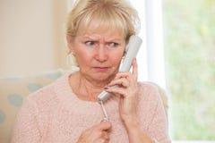 Ongerust gemaakte Hogere Vrouw die Telefoon thuis beantwoorden royalty-vrije stock afbeeldingen
