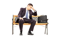 Ongerust gemaakte jonge businesspersonzitting op een houten bank Royalty-vrije Stock Afbeelding