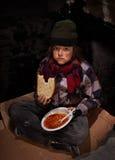 Ongerust gemaakte jonge dakloze jongen die liefdadigheidsvoedsel eten Stock Foto's