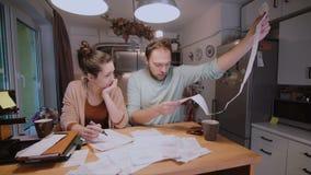 Ongerust gemaakte jonge familie die hun rekeningen in de keuken thuis bekijken Man en vrouw die binnenlandse rekeningen berekenen stock videobeelden