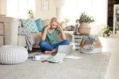 Ongerust gemaakte jonge vrouw die aan laptop thuis werken royalty-vrije stock foto's