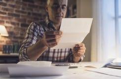 Ongerust gemaakte mens die zijn binnenlandse rekeningen thuis controleren royalty-vrije stock fotografie
