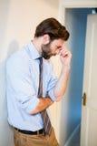 Ongerust gemaakte mens met hand op voorhoofd die op muur leunen Stock Afbeelding