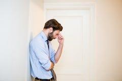 Ongerust gemaakte mens met hand op voorhoofd die op muur leunen Royalty-vrije Stock Foto