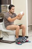 Ongerust gemaakte mensenzitting op het toilet dat uit loopt van stock foto