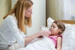 Ongerust gemaakte moeder die geneeskunde geven aan haar ziek jong geitje Stock Foto