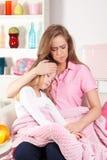 Ongerust gemaakte moeder met ziek kind stock foto