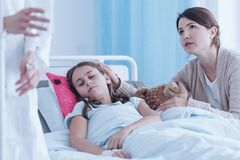 Ongerust gemaakte moeder ondersteunend zieke dochter royalty-vrije stock afbeelding